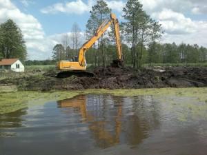 Koparka oczyszcza sztuczny zbiornik wodny